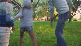 Los padres y dos hijas juegan deporte con la bola en parque de la primavera en el jardín floreciente Ocio activo almacen de video