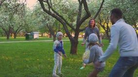 Los padres y dos hijas juegan deporte con la bola en parque de la primavera en el jardín floreciente Ocio activo almacen de metraje de vídeo