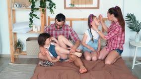 Los padres y dos hijas lindas se sientan en cama y pasan el tiempo junto, c?mara lenta almacen de video