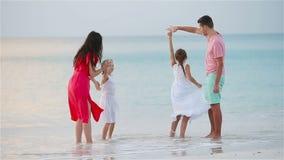 Los padres y los dos niños adorables se divierten mucho durante sus vacaciones de verano en la playa Familia de cuatro miembros e almacen de metraje de vídeo