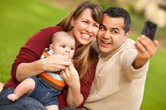 Los padres y el bebé de la raza mezclada toman su foto Imagen de archivo
