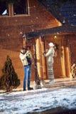 Los padres y el niño adornan a casa juntos al aire libre para la Navidad Imágenes de archivo libres de regalías