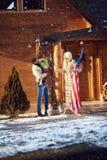 Los padres y el niño adornan la casa juntos al aire libre para la Navidad Imágenes de archivo libres de regalías