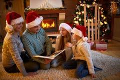 Los padres y los children's leyeron un libro en la chimenea en la Navidad e Fotografía de archivo