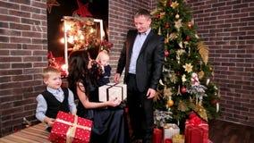 Los padres y los niños el día de fiesta, marido dan los regalos a su esposa y niños, fiesta de Navidad en la familia, padre almacen de video