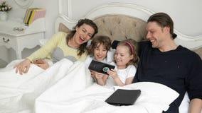Los padres y los niños están pasando el fin de semana juntos que miente en la cama La pequeña muchacha linda está mostrando algo  almacen de metraje de vídeo
