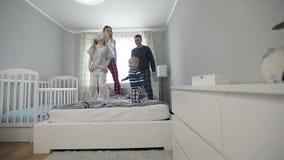 Los padres y los niños saltan en la cama almacen de video