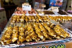Los palillos asados a la parrilla del calamar vendieron en el mercado de pescados de Tsukiji, Tokio, Japón Foto de archivo