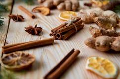 Los palillos de canela con anís protagonizan, el jengibre, naranjas secadas en el fondo de madera adornado con las ramas de árbol Fotografía de archivo