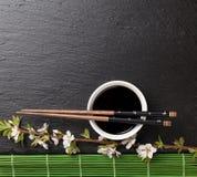 Los palillos del sushi, el cuenco de la salsa de soja y Sakura japoneses florecen Imagen de archivo