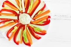 Los palillos vegetales coloridos en una placa con la inmersión sauce foto de archivo libre de regalías