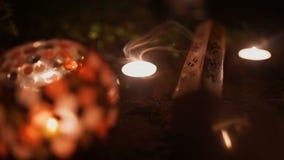 Los palillos y las velas del incienso están quemando y humo en fondo oscuro Humo de la luz del incienso y de la vela metrajes