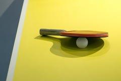 Los palos y las bolas de los tenis de mesa aislados en el fondo amarillo, p Foto de archivo