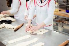 Los panaderos de las mujeres hacen los bollos de la pasta fotografía de archivo