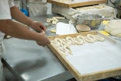 Los panaderos que hacían los pretzeles frescos en la pasta cubrieron la tabla Foto de archivo libre de regalías