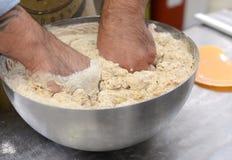 Los panaderos que hacen las barras de pan hechas a mano en una panadería de la familia que forma la pasta en tradional forman en  Imágenes de archivo libres de regalías