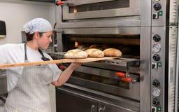 Los panaderos que hacen las barras de pan hechas a mano en una panadería de la familia que forma la pasta en tradional forman en  Fotos de archivo libres de regalías