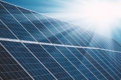 Los paneles de la planta de energía solar con los rayos del sol y el cielo azul Fotos de archivo