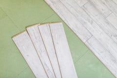 Los paneles de madera en el nuevo suelo laminado antes instalan fotos de archivo libres de regalías