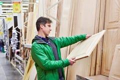 Los paneles de madera que hacen compras del hombre en tienda de DIY Imágenes de archivo libres de regalías