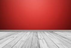 Los paneles de piso de madera blancos con el fondo rojo de la pared Imagenes de archivo