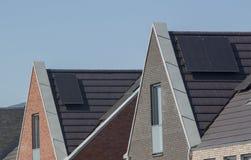 Los paneles de Sun en los tejados de nuevas casas imagen de archivo