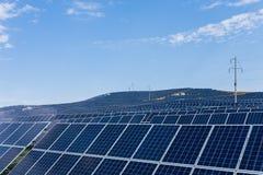 Los paneles fotovoltaicos y líneas de transmisión de arriba fotografía de archivo libre de regalías