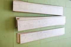 Los paneles grises de madera en el nuevo suelo laminado antes instalan fotografía de archivo libre de regalías