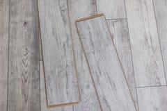 Los paneles grises de madera en el nuevo suelo laminado antes instalan imagenes de archivo