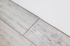 Los paneles grises de madera en el nuevo suelo laminado instalan en golpe fotos de archivo