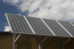 Los paneles solares con el cielo azul y las nubes Imagen de archivo libre de regalías