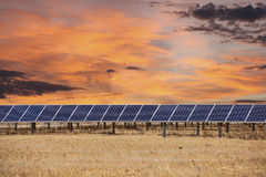 Los paneles solares con las nubes de la salida del sol Imagen de archivo libre de regalías