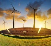 Los paneles solares con las turbinas de viento en la puesta del sol Fotografía de archivo libre de regalías