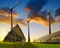 Los paneles solares con las turbinas de viento en la puesta del sol Fotos de archivo libres de regalías