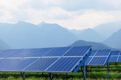 Los paneles solares contra las montañas Imagen de archivo