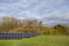 Los paneles solares en campo con los árboles y el cielo nublado imágenes de archivo libres de regalías