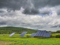 Los paneles solares en campo del diente de león Imagen de archivo libre de regalías