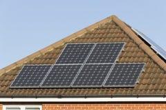 Los paneles solares en dos aspectos del tejado de la casa Imágenes de archivo libres de regalías
