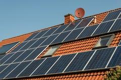Los paneles solares en una azotea roja Fotos de archivo