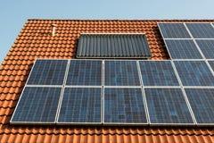 Los paneles solares en una azotea roja Fotografía de archivo