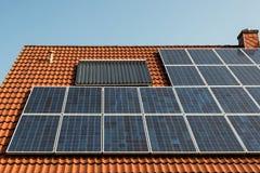 Los paneles solares en una azotea roja Imagen de archivo