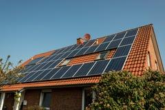 Los paneles solares en una azotea roja Foto de archivo