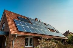 Los paneles solares en una azotea roja Imagen de archivo libre de regalías