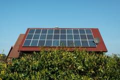 Los paneles solares en una azotea roja Imagenes de archivo