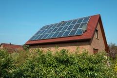Los paneles solares en una azotea roja Fotografía de archivo libre de regalías