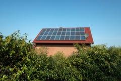 Los paneles solares en una azotea roja Foto de archivo libre de regalías
