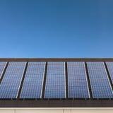 Los paneles solares en una fila en una azotea con un cielo azul Fotografía de archivo