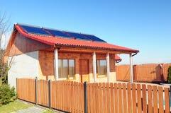Los paneles solares en una pequeña casa Foto de archivo libre de regalías