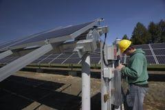 Los paneles solares revisados por el trabajador Fotografía de archivo