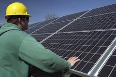 Los paneles solares revisados por el trabajador Imagenes de archivo